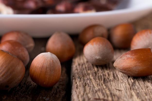Pezzi del cioccolato con le nocciole sul fondo di legno del piatto bianco. avvicinamento.