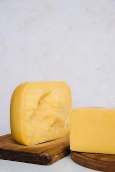 Pezzi del formaggio gouda sul tagliere di legno contro il contesto strutturato di marmo