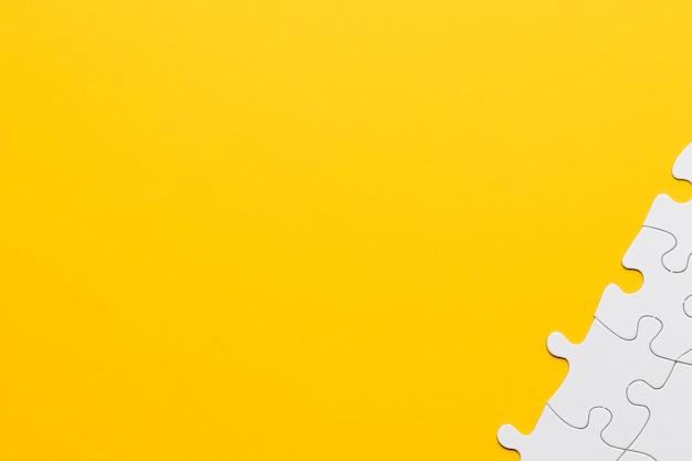 Pezzi del puzzle bianco all'angolo dello sfondo giallo