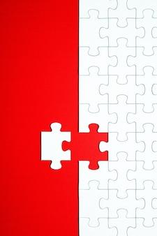 Pezzi del puzzle bianco su uno sfondo rosso separato