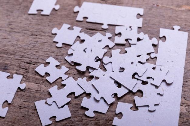 Pezzi del puzzle che si trovano sui bordi rustici di legno anziani. concettuale di innovazione, ricerca di soluzioni e integrazione.