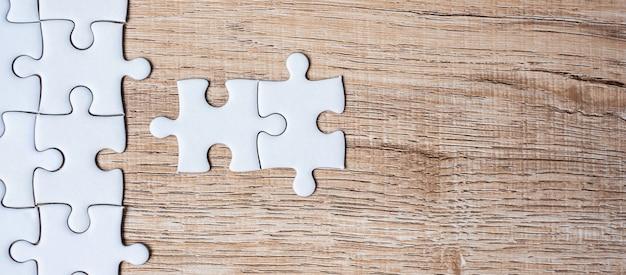 Pezzi del puzzle su sfondo di tavolo in legno. soluzioni aziendali, obiettivi della missione, successo, obiettivi, cooperazione, partenariato e strategia