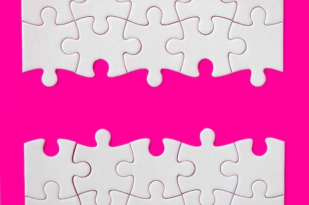 Pezzi del puzzle su sfondo fucsia