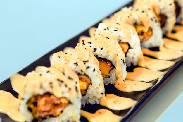 Pezzi deliziosi di sushi su un piatto con salsa con fondo blu