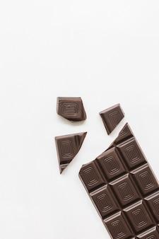 Pezzi di barretta di cioccolato fondente isolato su sfondo bianco