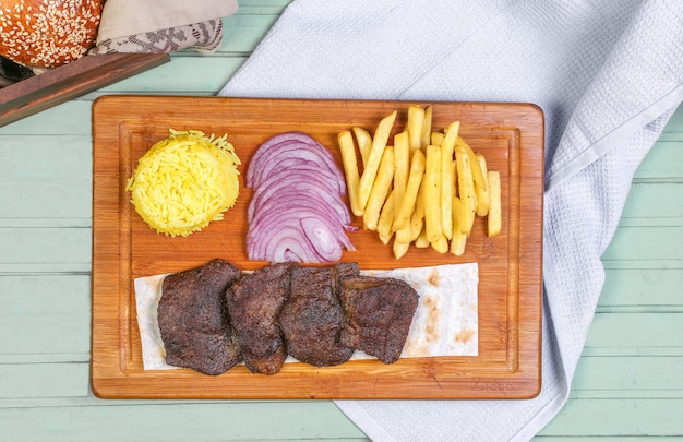 Pezzi di bistecca di carne con patatine fritte, cipolla e riso sul bordo di legno.