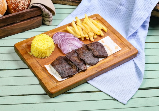 Pezzi di bistecca di carne con patatine fritte, cipolla e riso.
