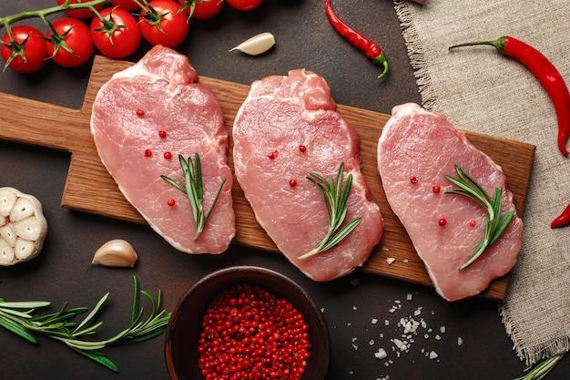 Pezzi di bistecca di maiale cruda su tagliere con pomodori ciliegia, rosmarino, aglio, pepe, sale e spezie mortaio su sfondo marrone arrugginito