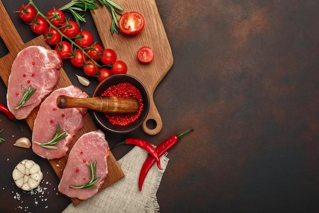 Pezzi di bistecca di maiale crudo su tagliere con pomodorini, rosmarino, aglio, pepe, sale e spezie mortaio