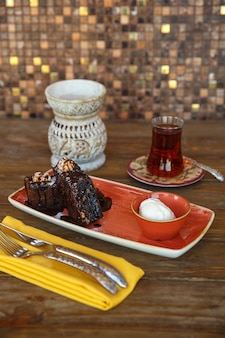 Pezzi di brownie con gelato alla vaniglia servito con tè nero