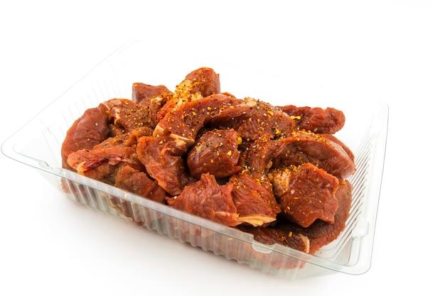 Pezzi di carne cruda, gulasch in un vassoio di plastica, cosparso di spezie. su sfondo bianco
