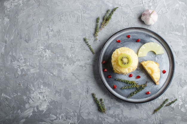 Pezzi di carne di maiale al forno con ananas, formaggio e kiwi sul piatto grigio.