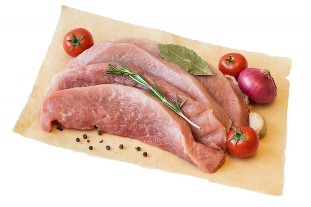 Pezzi di carne suina fresca con i pomodori e le spezie su un foglio di carta isolato su fondo bianco.
