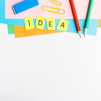 Pezzi di carta gialli con il testo di idea con i rifornimenti di scuola isolati su fondo bianco