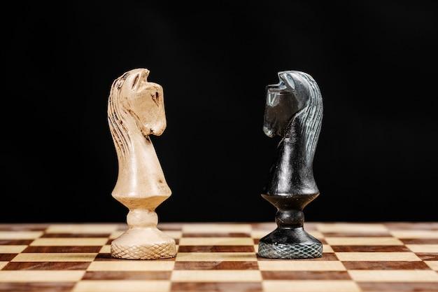 Pezzi di cavalieri uno di fronte all'altro su una scacchiera