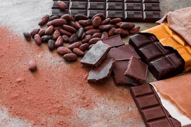 Pezzi di cioccolato, fave di cacao e polvere sul tavolo