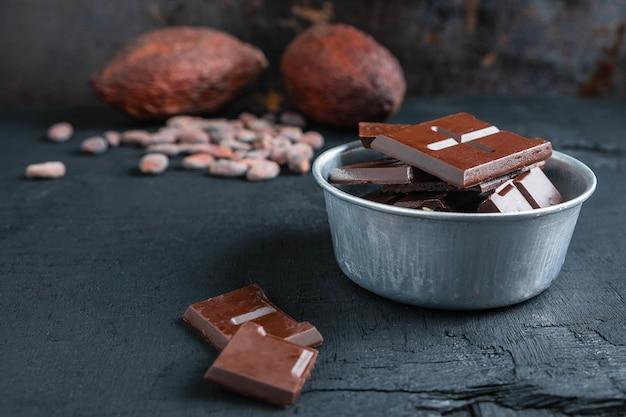 Pezzi di cioccolato fondente e fave di cacao sul tavolo