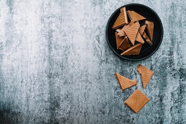 Pezzi di cioccolato in una ciotola su sfondo stagionato
