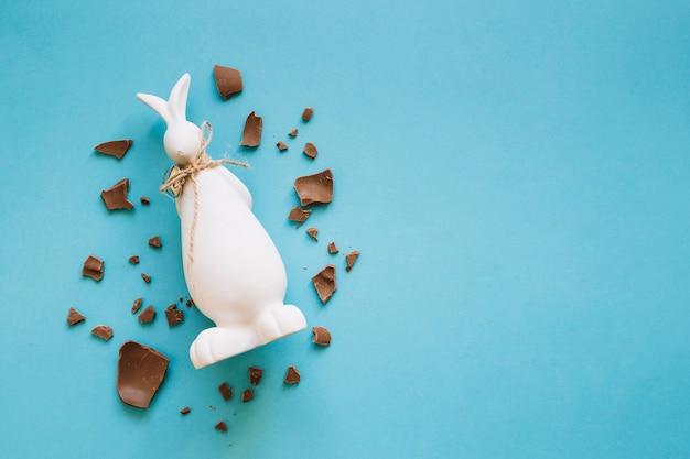 Pezzi di cioccolato intorno a statuetta di coniglio