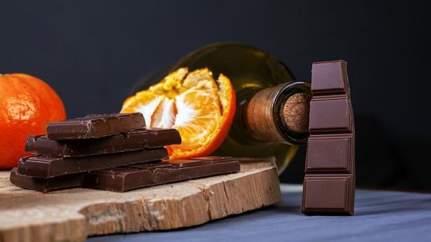 Pezzi di cioccolato, mandarini e una bottiglia di vino su un piatto di legno. vin brulè ingredienti.