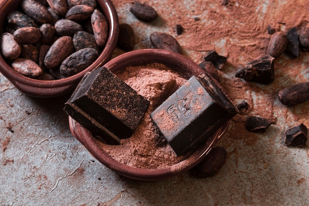 Pezzi di cioccolato su polvere di cacao e fagioli sopra il tavolo