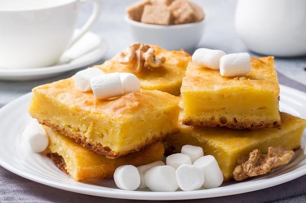 Pezzi di deliziosa torta di zucca con marshmallow e noci su un piatto