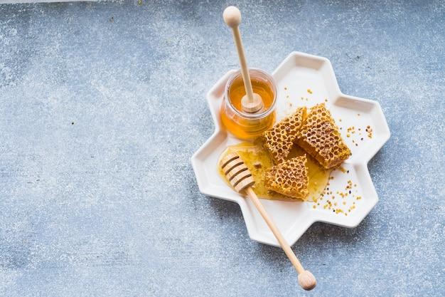 Pezzi di favo con vasetto di miele nel vassoio bianco su sfondo strutturato