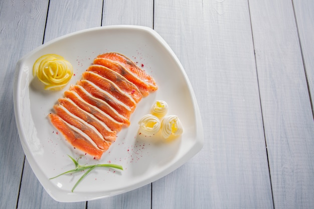 Pezzi di filetto di salmone crudo servito con spezie, limone, burro ed erbe sul piatto bianco e tavolo in legno