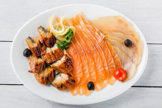 Pezzi di filetto di salmone, grongo, pezzi di storione serviti con limone, olive nere, erbe e pomodoro ciliegia sul piatto bianco e tavolo in legno