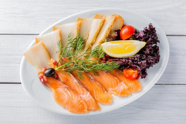 Pezzi di filetto di salmone, pezzi di storione serviti con limone, olive nere, erbe aromatiche, pomodorini e semi di melograno sul piatto bianco e tavolo in legno