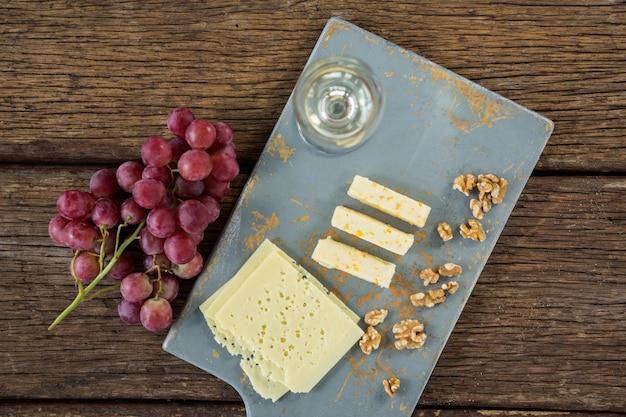 Pezzi di formaggio, noci, uva e bicchiere di vino sul vassoio