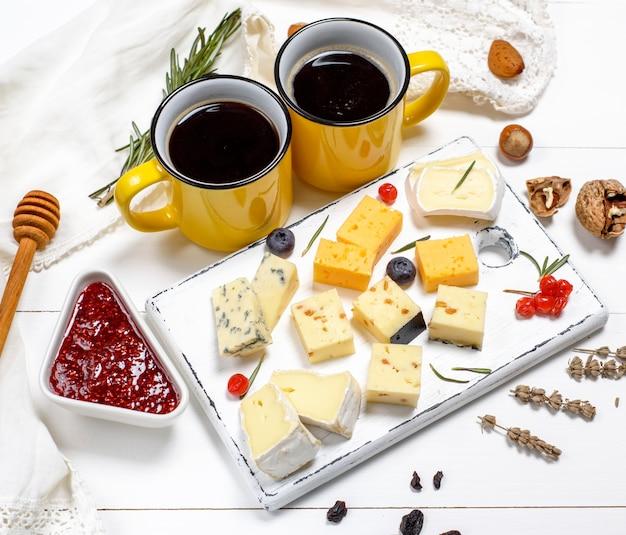 Pezzi di formaggio su una tavola di legno bianca