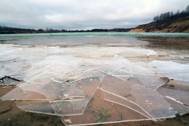 Pezzi di ghiaccio sottile sull'acqua di una cava di sabbia. regione di leningrado.