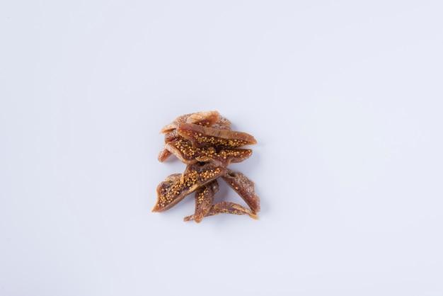 Pezzi di gustoso fico secco su sfondo bianco