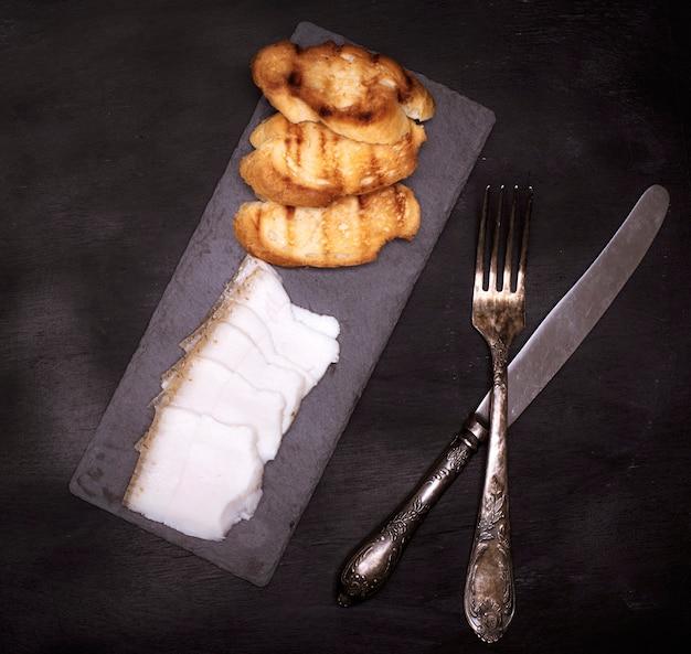 Pezzi di lardo e pane tostato