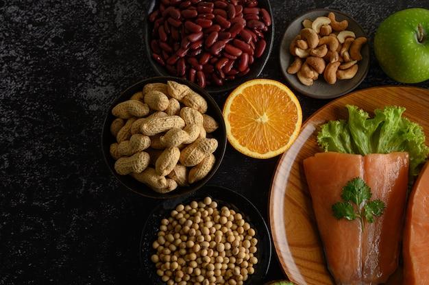Pezzi di legumi, frutta e salmone su un piatto di legno.