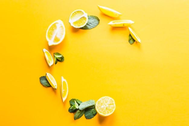 Pezzi di limone, lime e foglie di menta verde allineati in un cerchio