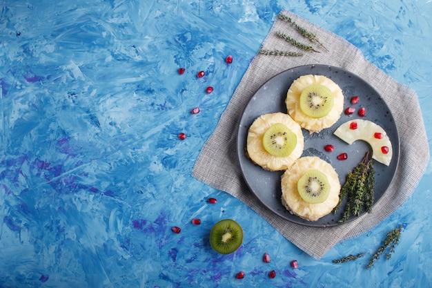 Pezzi di maiale al forno con ananas, formaggio e kiwi