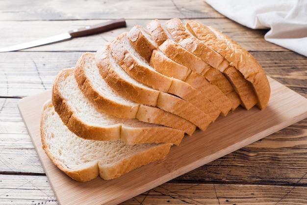 Pezzi di pagnotta di pane bianco per pane tostato su un tavolo di legno.