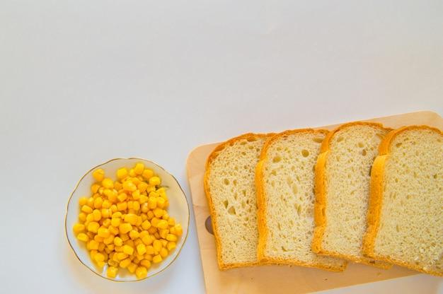Pezzi di pane di mais fresco a fette su una tavola di legno e un piatto di chicchi di mais sul tavolo