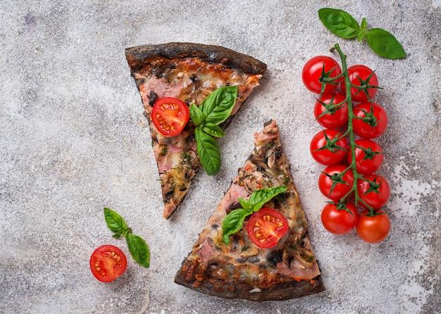 Pezzi di pizza nera con pomodori e basilico