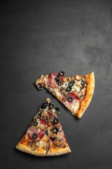 Pezzi di pizza su tavola di legno nero scuro, pizza italiana tradizionale