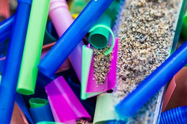 Pezzi di plastica del primo piano raccolti dalla sabbia
