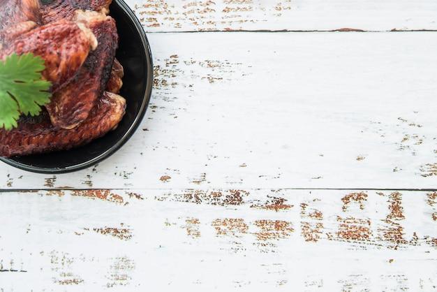 Pezzi di pollo alla griglia deliziosi in ciotola sulla tavola di legno