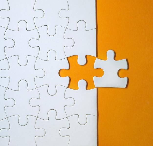 Pezzi di puzzle bianco incompiuto su sfondo arancione