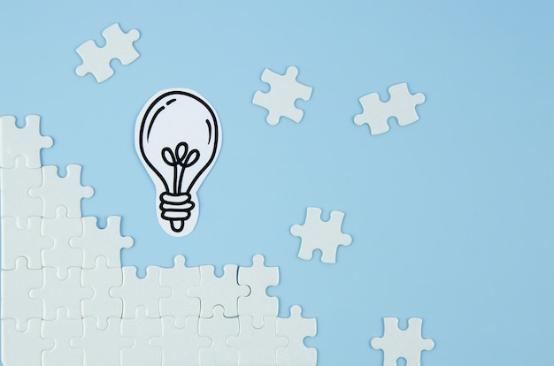 Pezzi di puzzle con lampadina su sfondo blu