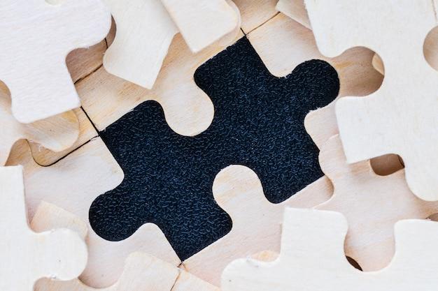 Pezzi di puzzle in legno su sfondo nero