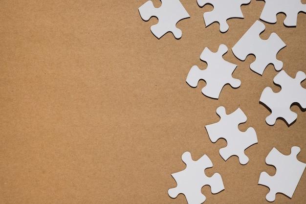 Pezzi di un puzzle bianco su sfondo di carta marrone