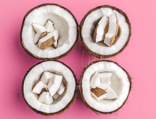 Pezzi rotti della noce di cocco su fondo rosa luminoso, vista superiore, spazio della copia