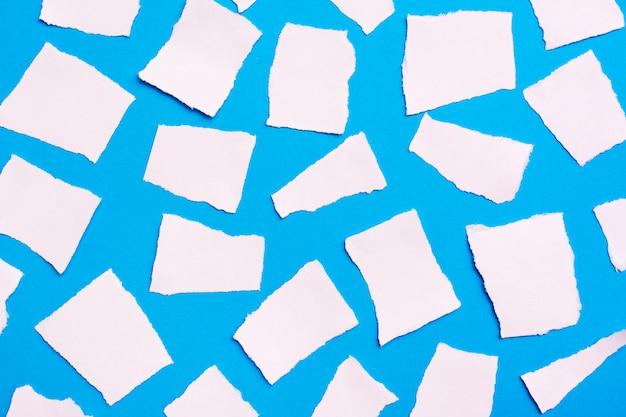 Pezzi strappati di carta bianca bianca disposti a caso su uno sfondo di cartone blu. vista dall'alto